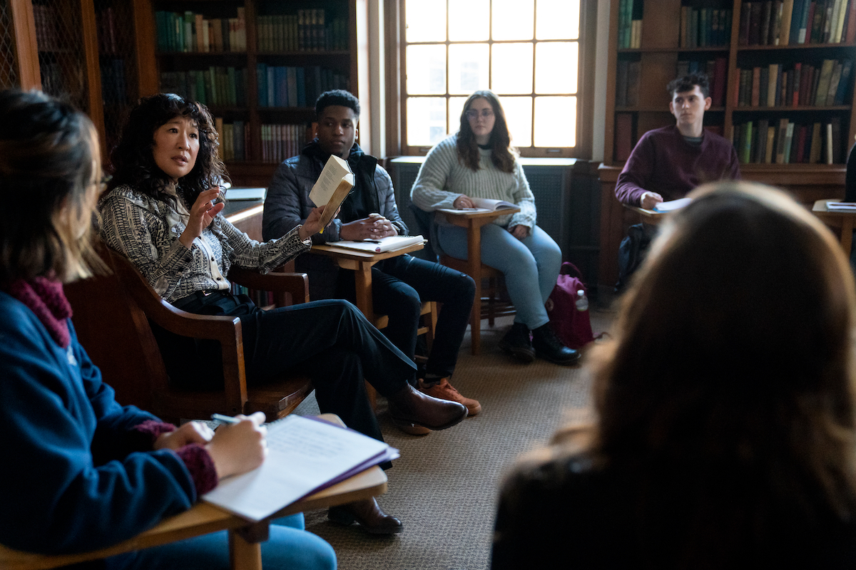 Sandra Oh sits in a chair reading from a book as students sit in desks around her in 'The Chair' Season 1 Episode 6