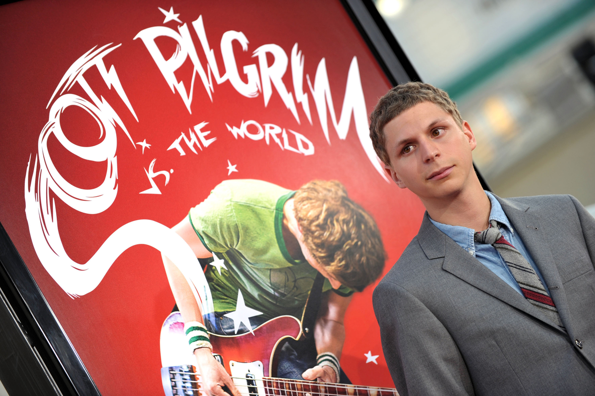 Michael Cera at the 'Scott Pilgrim vs. the World' premiere in front of a movie poster