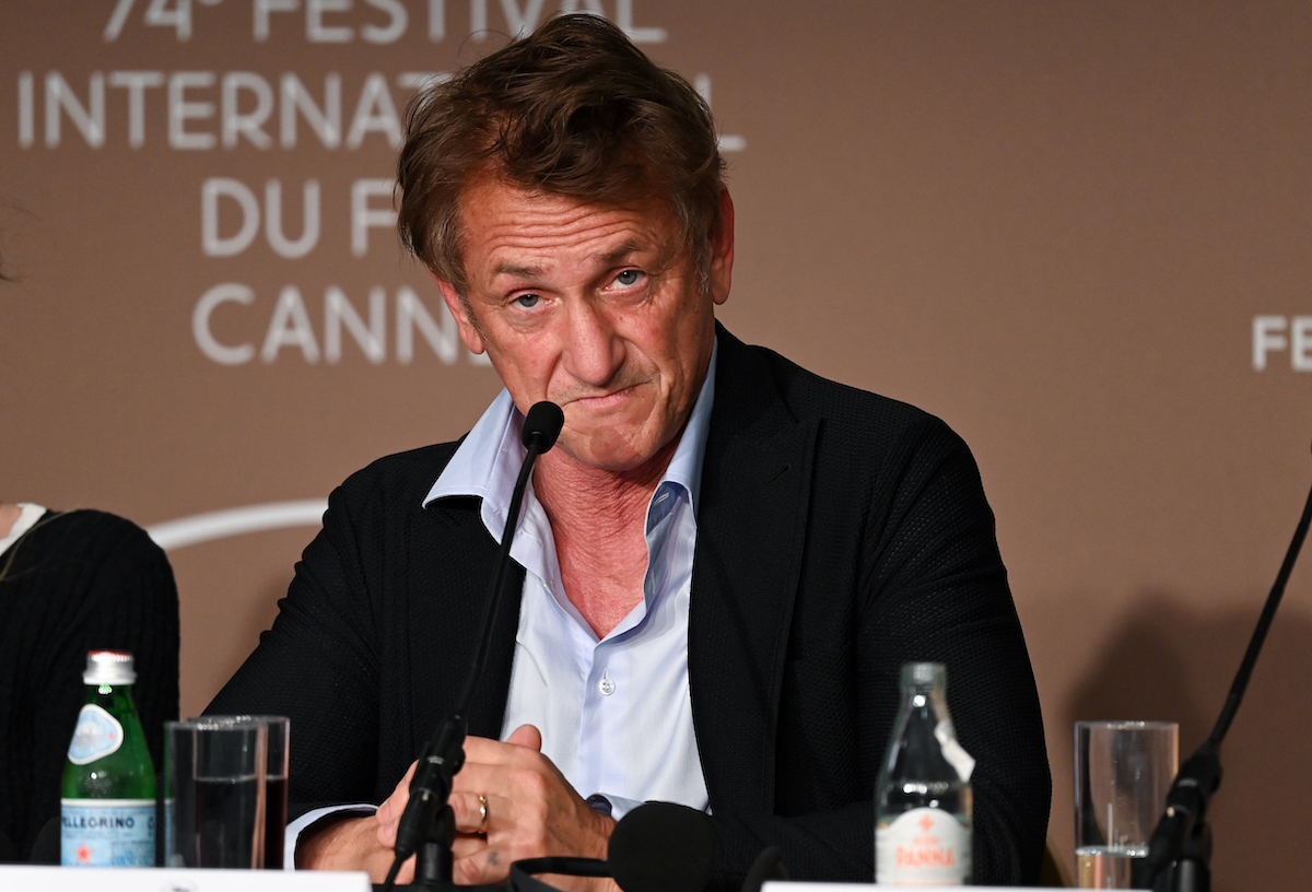 Sean Penn sitting near a microphone.