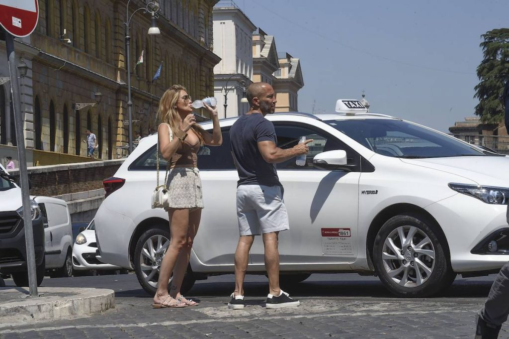 Chrishell Stause sips a water bottle while waiting outside of a car with Jason Oppenheim in Italy in July 2021