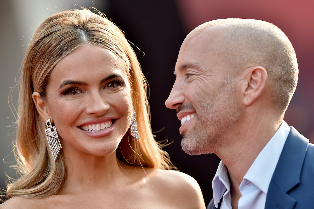 Jason Oppenheim smiles at Chrishell Stause on the red carpet in August 2021