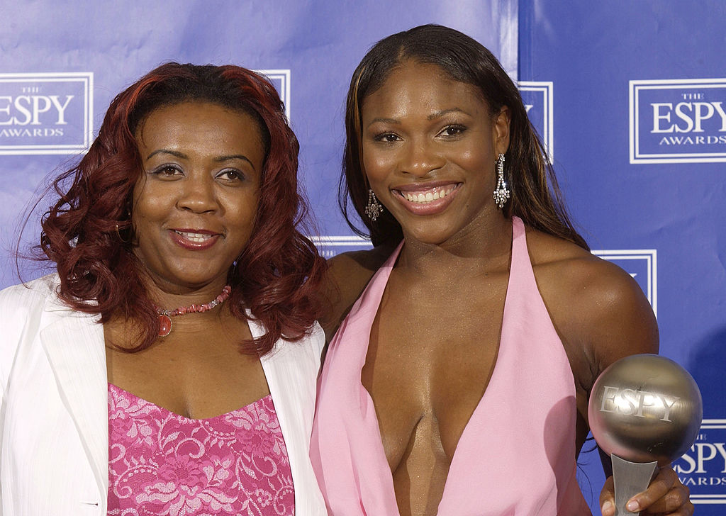 Serena Williams and Yetunde Price pose on stage all smiles. Both are wearing pink dresses.