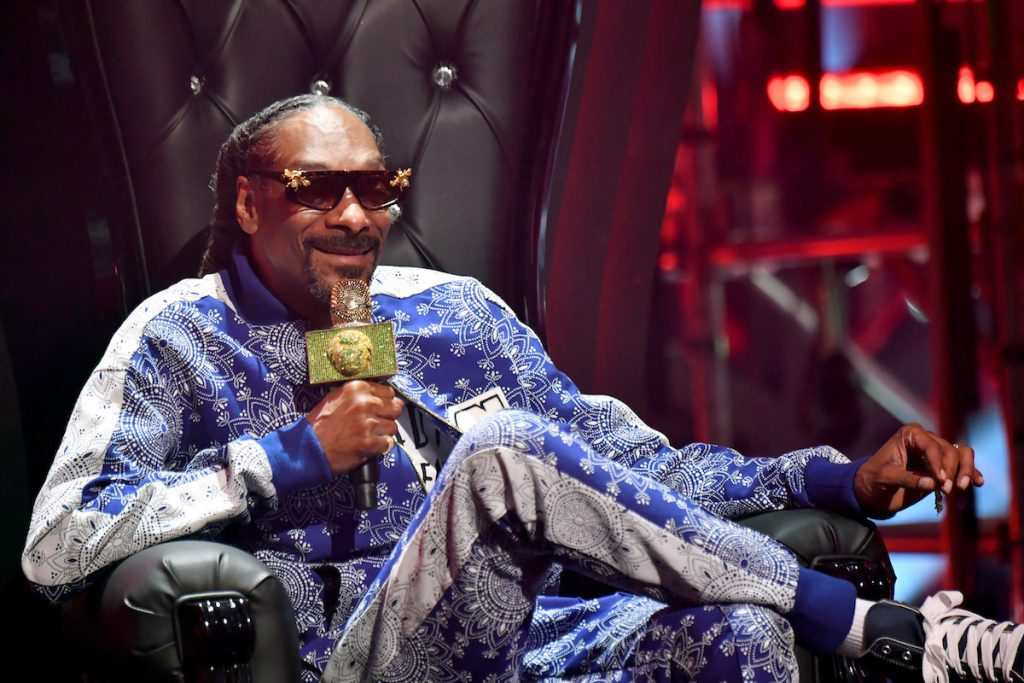 Snoop Dogg sits with his legs crossed and wearing sunglasses, smiling and talking into a microphone.