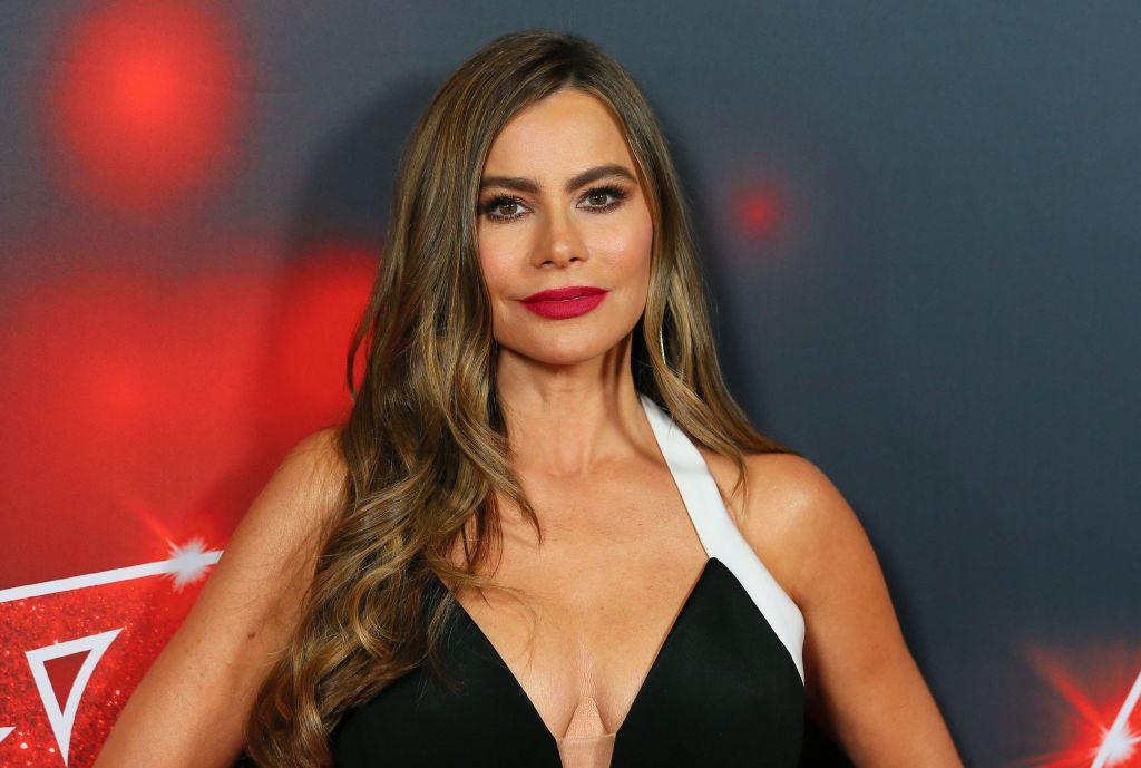 Sofia Vergara walks the red carpet in a black dress with a white halter strap.