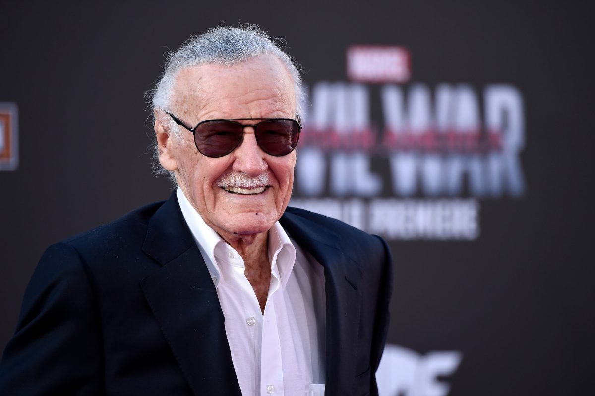 Marvel's Stan Lee wearing a black suit and smiling in front of a 'Captain America: Civil War' wall