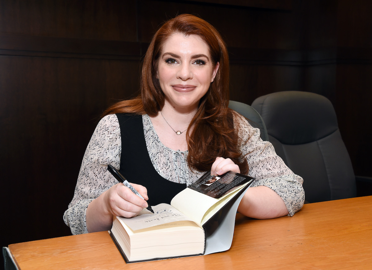 'Twilight' author Stephenie Meyer signs a book and smiles.