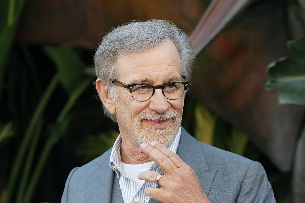 Steven Spielberg smiles and poses in a gray suit