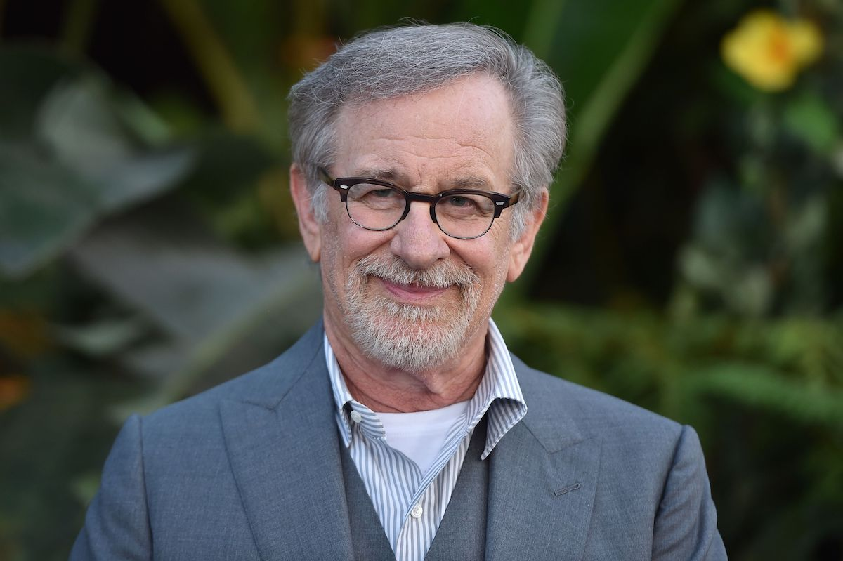 Steven Spielberg wears a gray suit and smiles in front of a leafy background