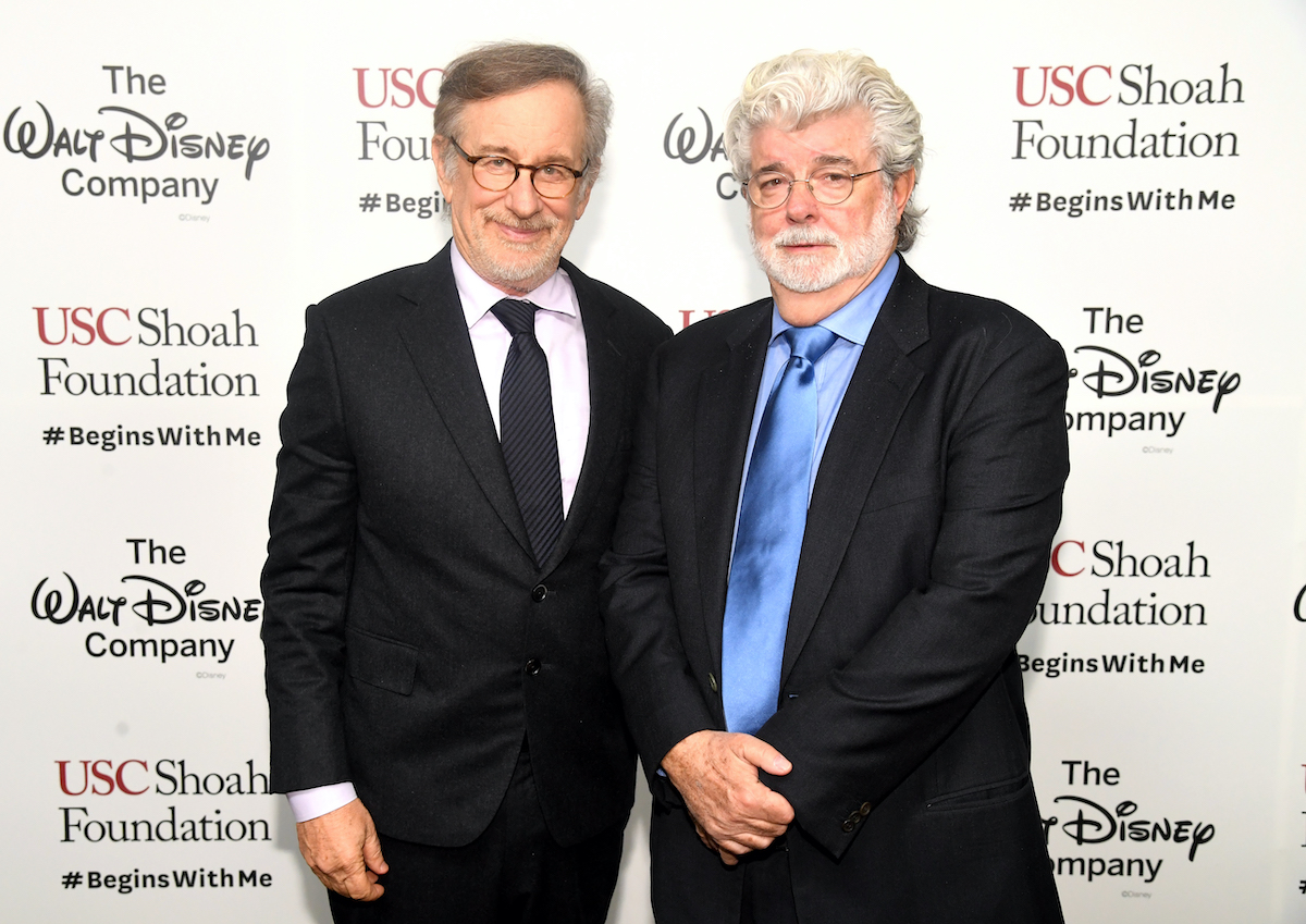 Steven Spielberg and George Lucas wear suits and pose on the red carpet