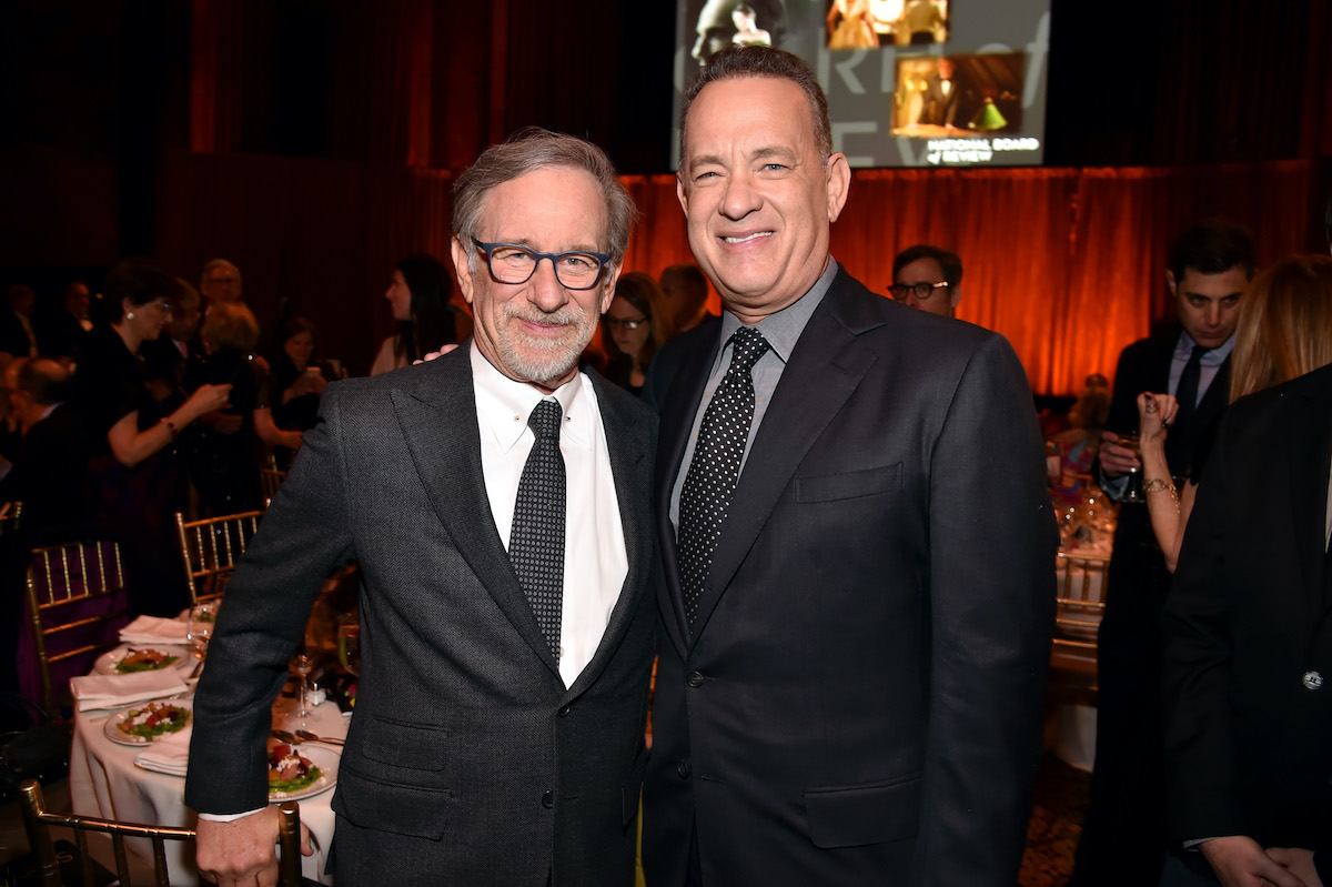 Steven Spielberg and Tom Hanks wear suits and pose