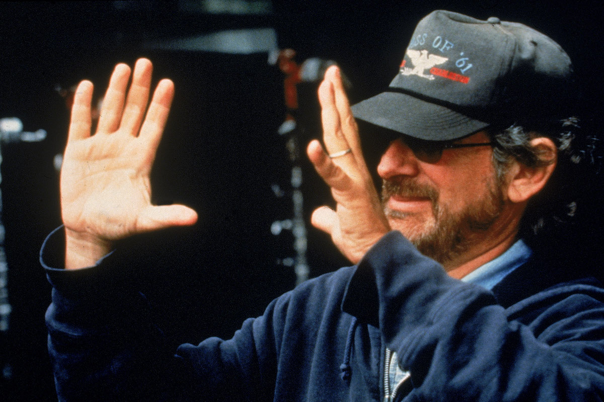 Steven Spielberg holds his hands up while directing a scene