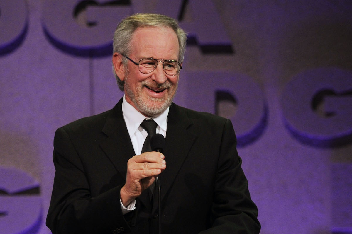 Steven Spielberg holds a mic while speaking onstage