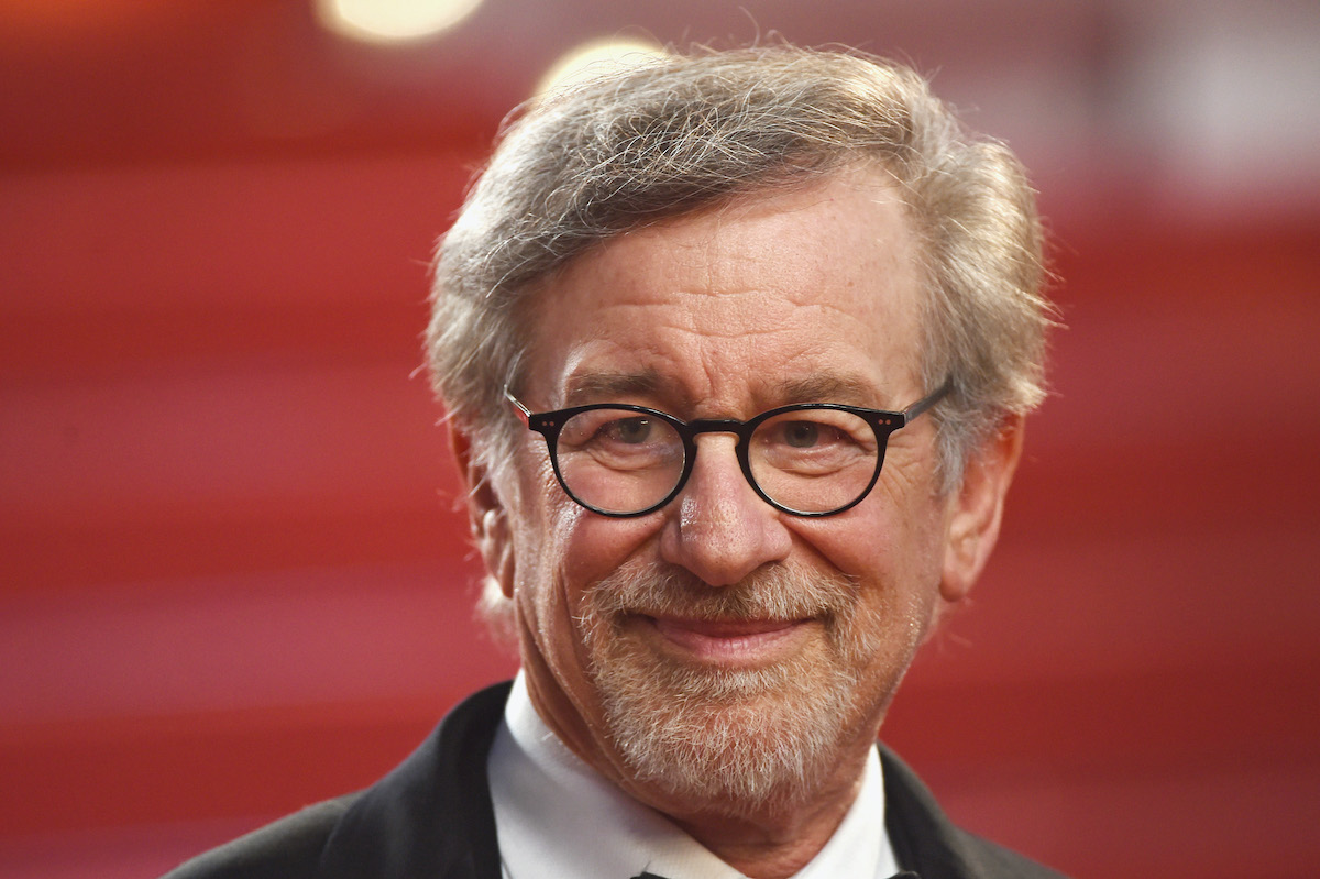Steven Spielberg smiles amid a red background