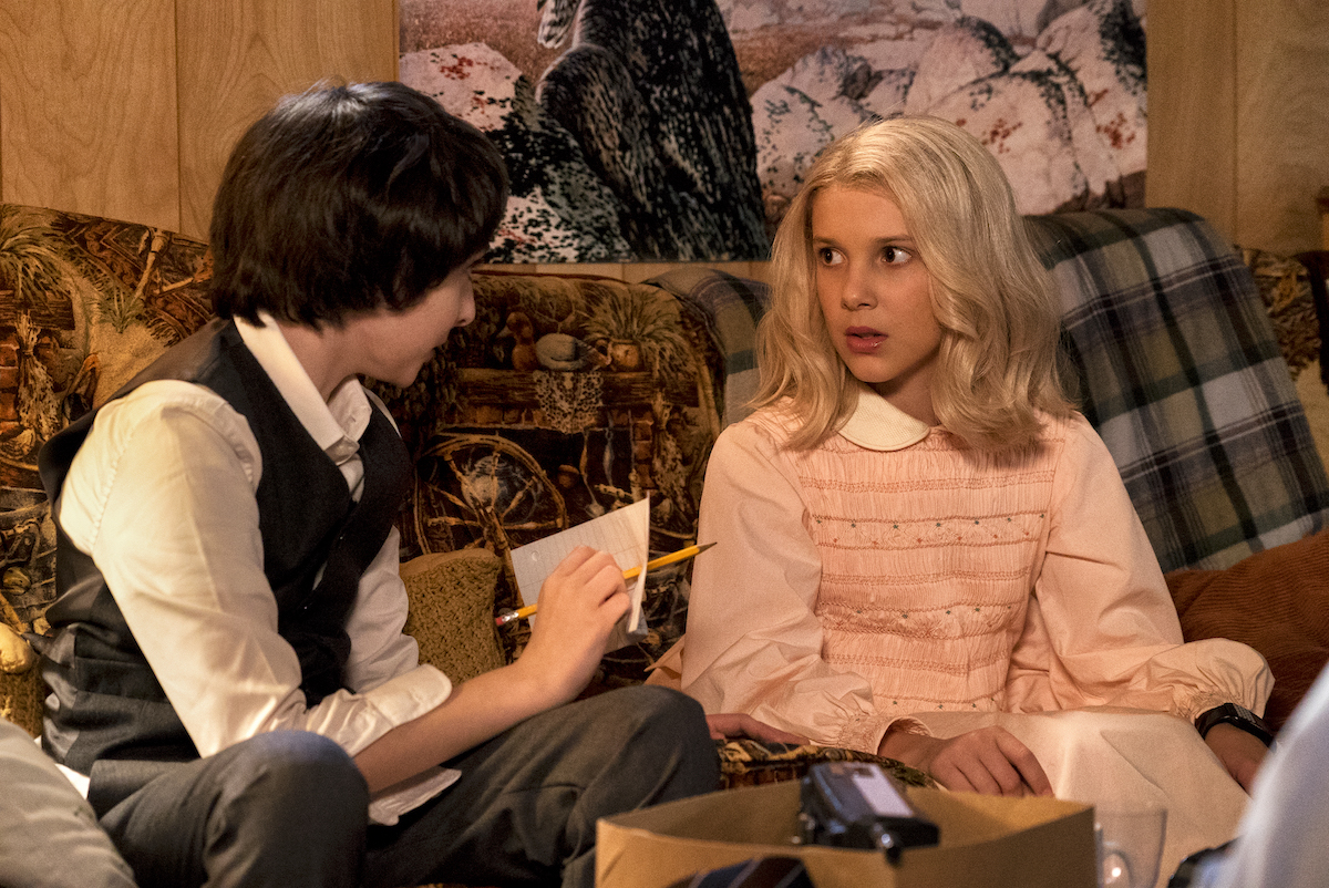 Mike look at Eleven in a pink dress and a wig in a production still f