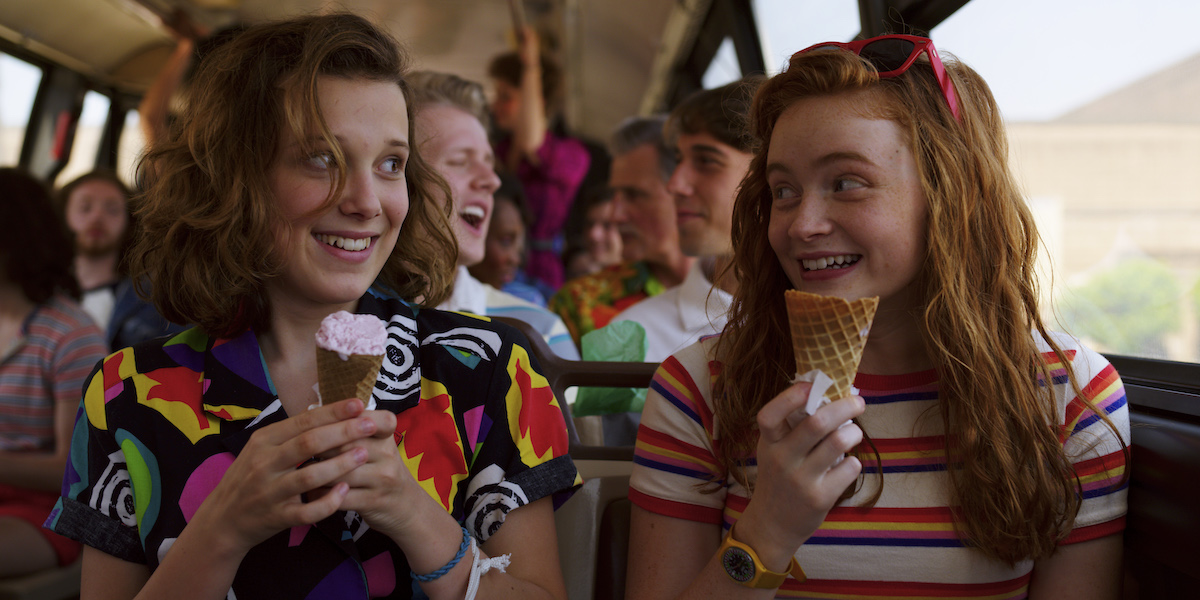 The newest 'Stranger Things' Season 4 trailer has fans taking note of Eleven's haircut. In this season 3 image of Eleven (Millie Bobby Brown) and Max (Sadie Sink) looking at each other on a bus wearing colorful '80s style clothing.