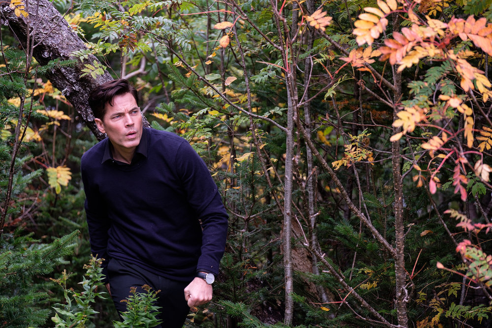 'SurrealEstate' production still with Tim Rozon as Nick Roman in a wooded area