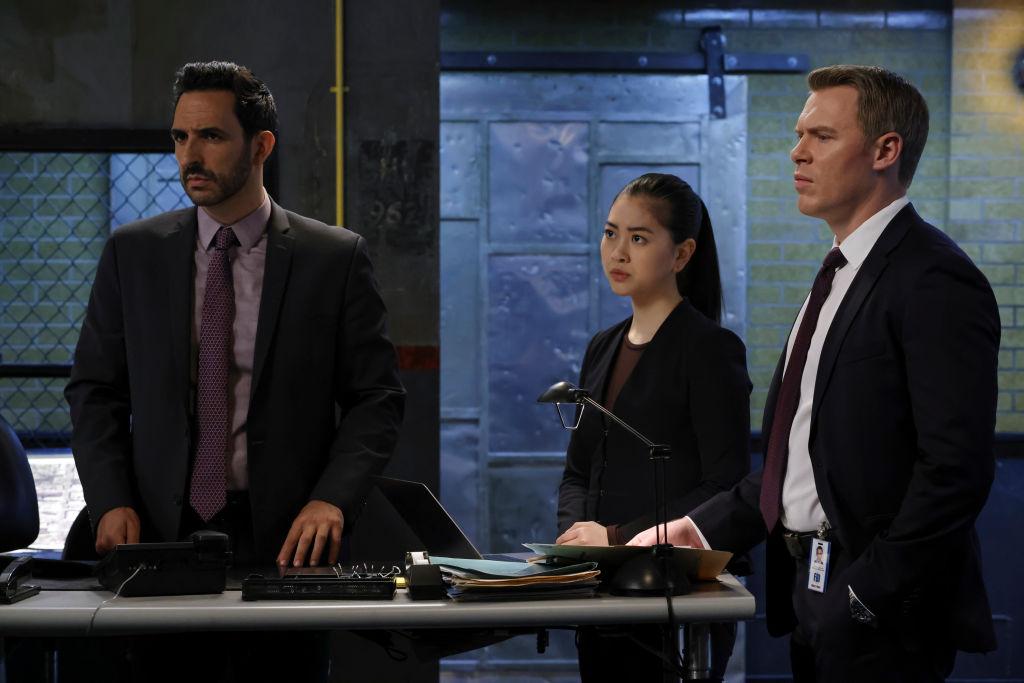 Amir Arison as Aram Mojtabai, Laura Sohn as Agent Alina Park, and Diego Klattenhoff as Donald Ressler stand in the FBI task force room together.
