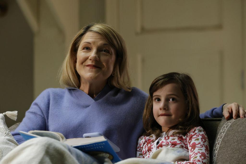 Victoria Clarke dans le rôle de Mme French, Hazel et Ginger Mason dans le rôle d'Agnes Kane assis sur une toux ensemble en lisant un livre.