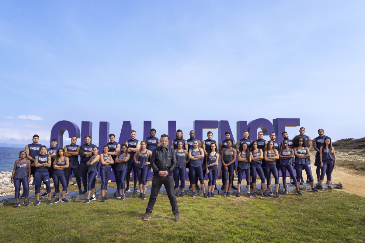 The cast of MTV's 'The Challenge' Season 37 all standing outside in front of the show's sign with host T.J. Lavin in front of them