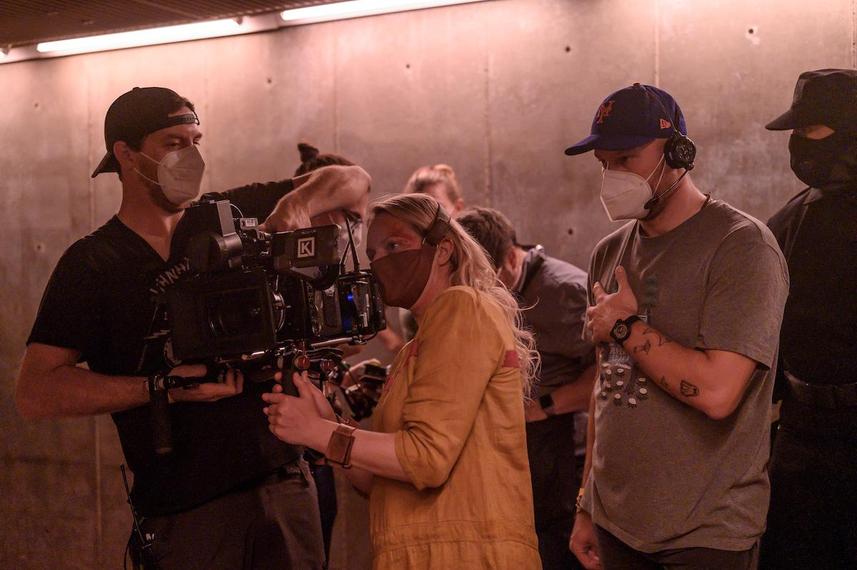 Elisabeth Moss and crew behind-the-scenes of 'The Handmaid's Tale' Season 4 Episode 3, 'The Crossing.' Moss directed this episode. And in the photo, she's dressed as June, who's being tortured in a high-security Gilead prison and wearing a mask and yellow prison dress. Moss is looking at playback on a video camera and is surrounded by other crew members dressed in casual clothing and masks.