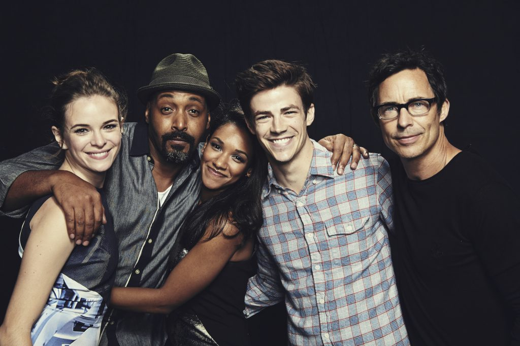 Cast members of 'The Flash' smiling in front of a black curtain
