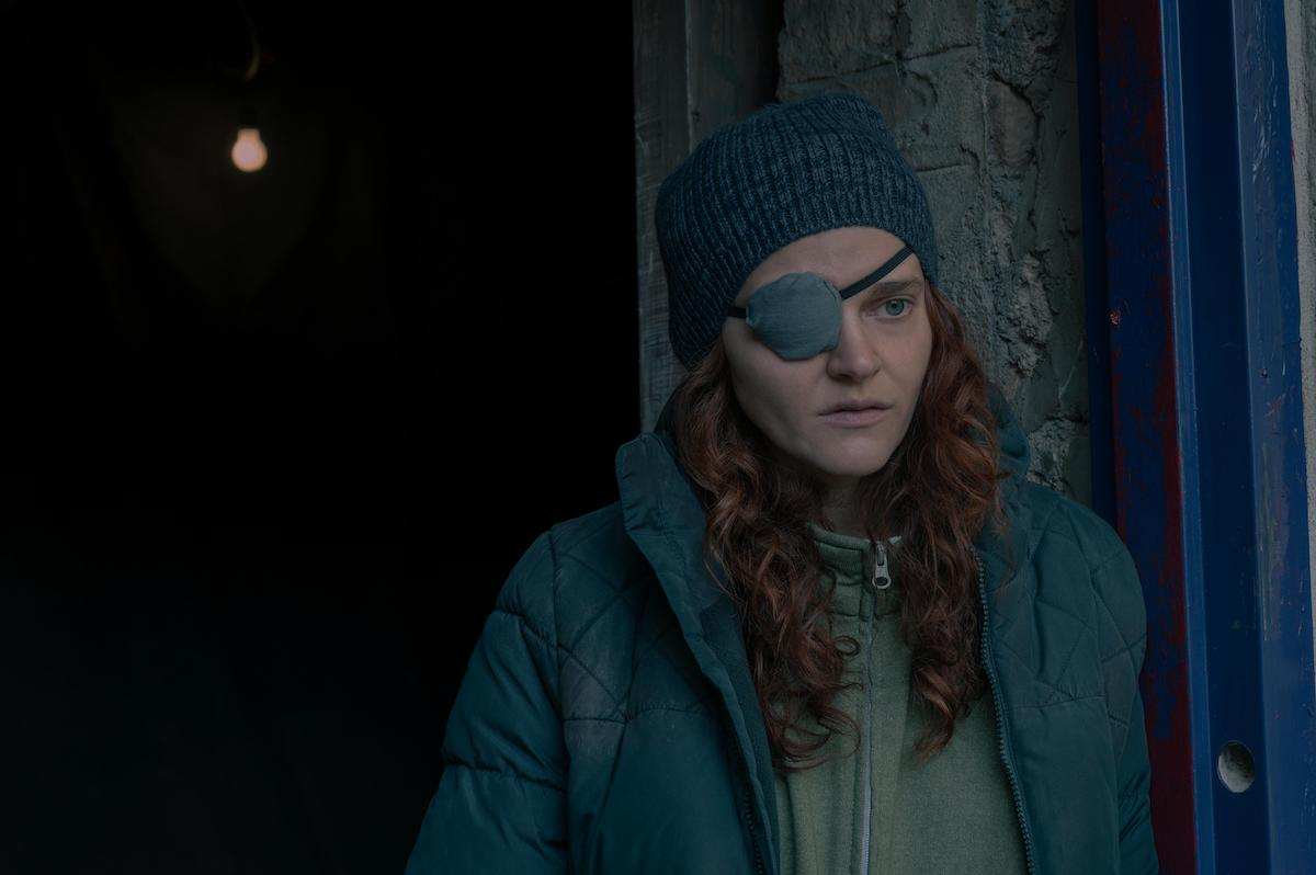 Madeline Brewer as Janine in 'The Handmaid's Tale' Season 4 Episode 5, 'Chicago.' She wears a grey zip-up hoodie with a thin, faded blue puffer jacket over it. She also wears a grey knit beanie and a grey eyepatch with a black strap as she stands in a blue and grey doorway. 'The Handmaid's Tale' Season 4 revealed Janine's backstory in episode 4, 'Milk,' which helped fans understand her more in 'The Handmaid's Tale' 'Chicago' episode.