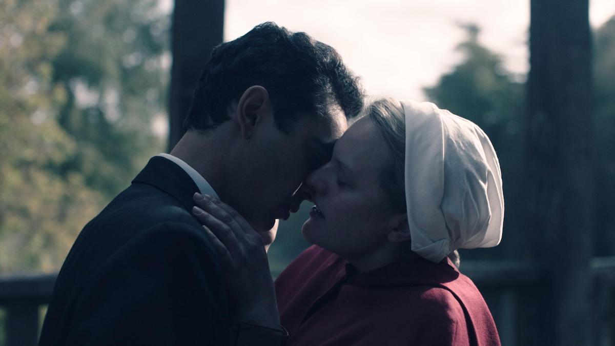 Elisabeth Moss and Max Minghella in 'The Handmaid's Tale' Season 4 Episode 2, 'Nightshade.' June stages an attack on a group of commanders in the episode but pays a price for it later. She's reunited with Nick in this photo. She's wearing her red Handmaid uniform and white bonnet as she leans in to kiss Nick, who's wearing a black suit. They're on a wooden bridge in daytime with trees surrounding.