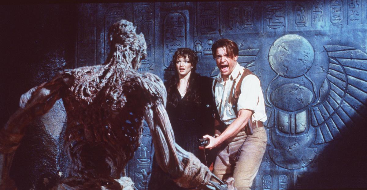 Rick O'Connell (Brendan Fraser) cầm súng khi xác ướp tiếp cận anh ta và Evelyn (Rachel Weisz) trong The Mummy 1999