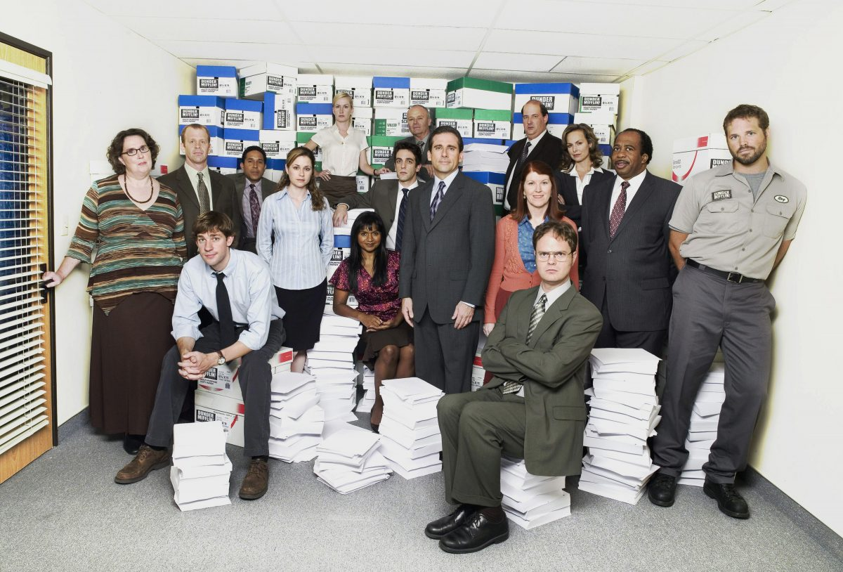 """The cast of """"The Office' –one of the premier comedy shows – poses for a photo around stacks if Dunder Mifflin paper"""