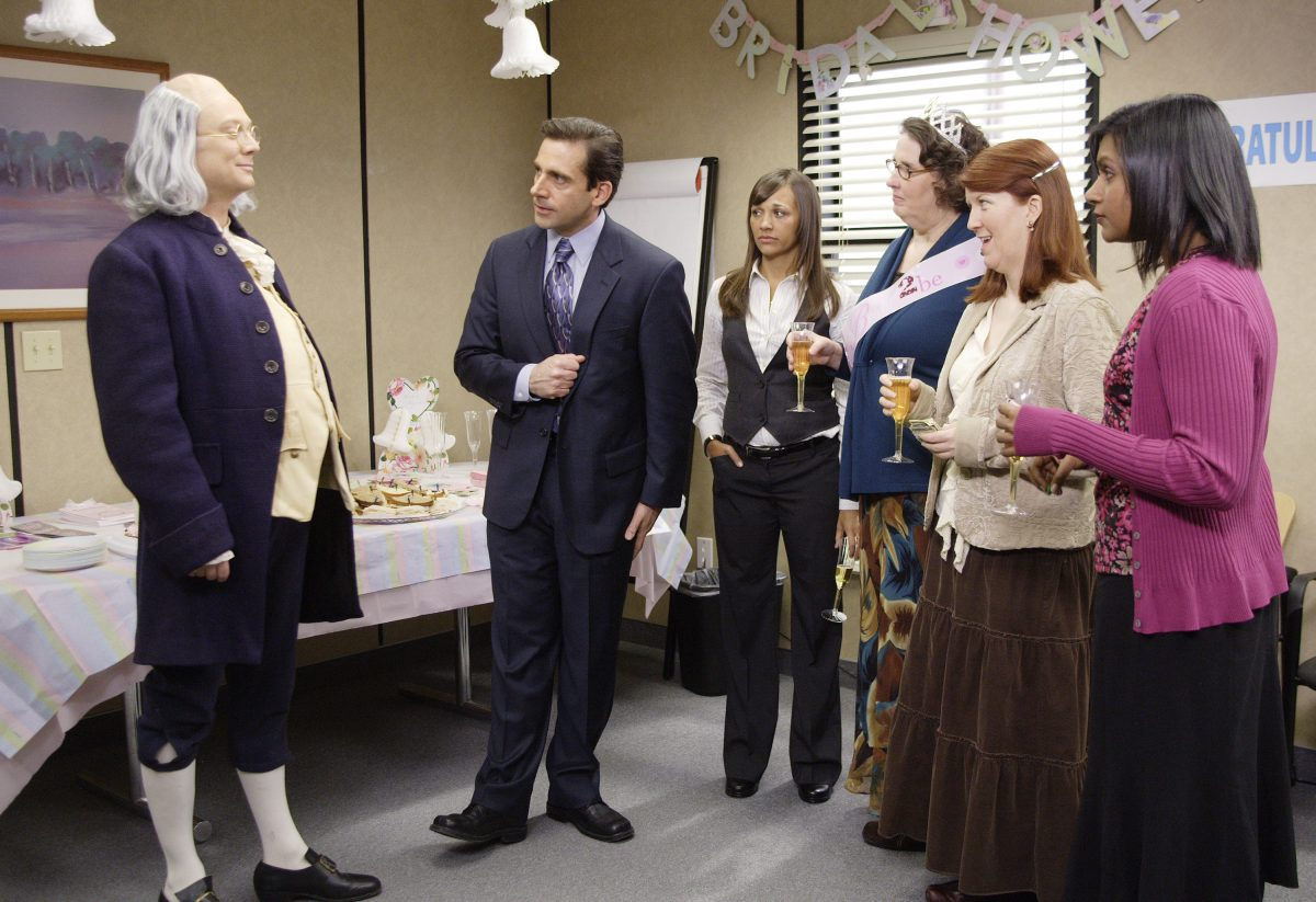 Steve Carell laughs at a Benjamin Franklin impersonator in a scene from 'The Office.'