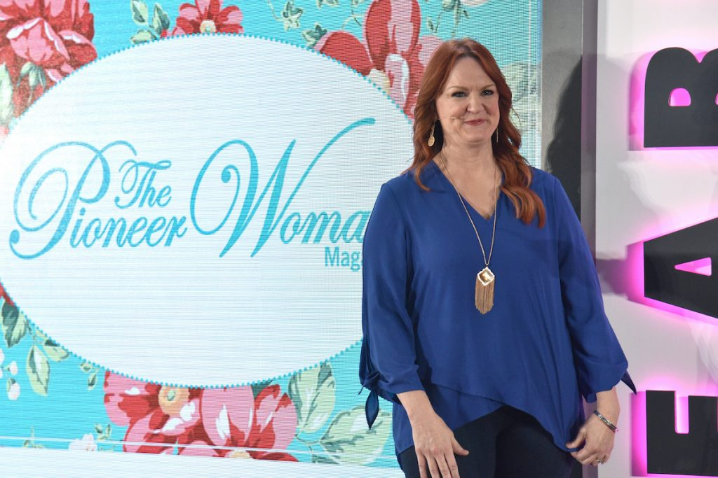 Ree Drummond smiles in front of The Pioneer Woman Magazine sign