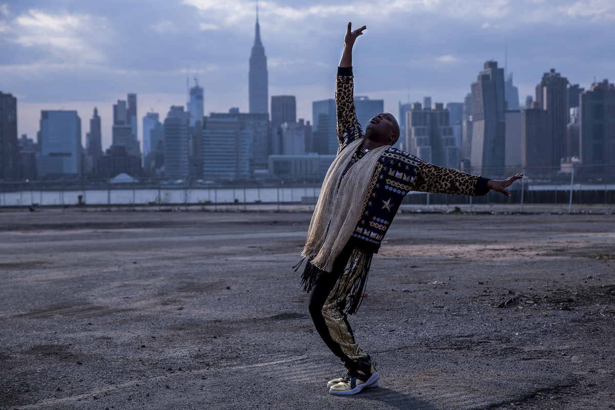 'Unbreakable Kimmy Schmidt' episode titled 'Kimmy Fights a Fire Monster!' titus posing in front of the New York City skyline