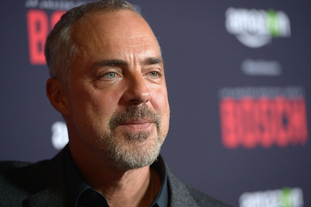 Titus Welliver walks the red carpet in a dark suit. 'Bosch' is written on the wall behind him.