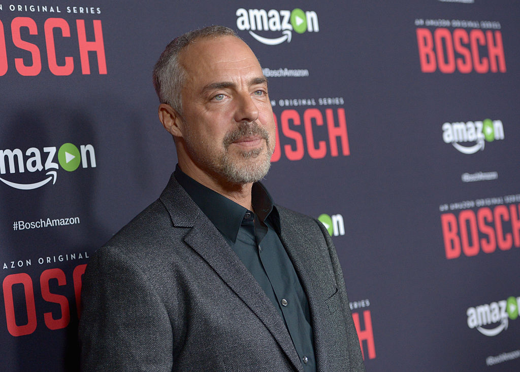 Titus Welliver walks the red carpet in a dark suit. The 'Bosch' title is on the wall behind him.
