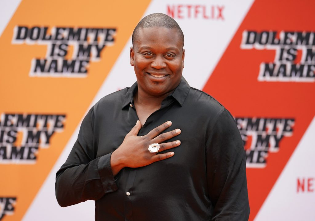 Tituss Burgess smiles for the camera with his hand on his heart.