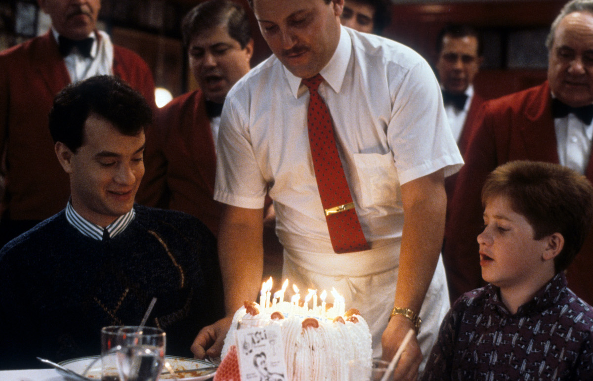 Tom Hanks sitting at a dining table as a birthday cake is being delivered in 'Big'