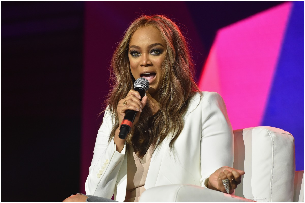 Tyra Banks holding a microphone and speaking while attending an event.