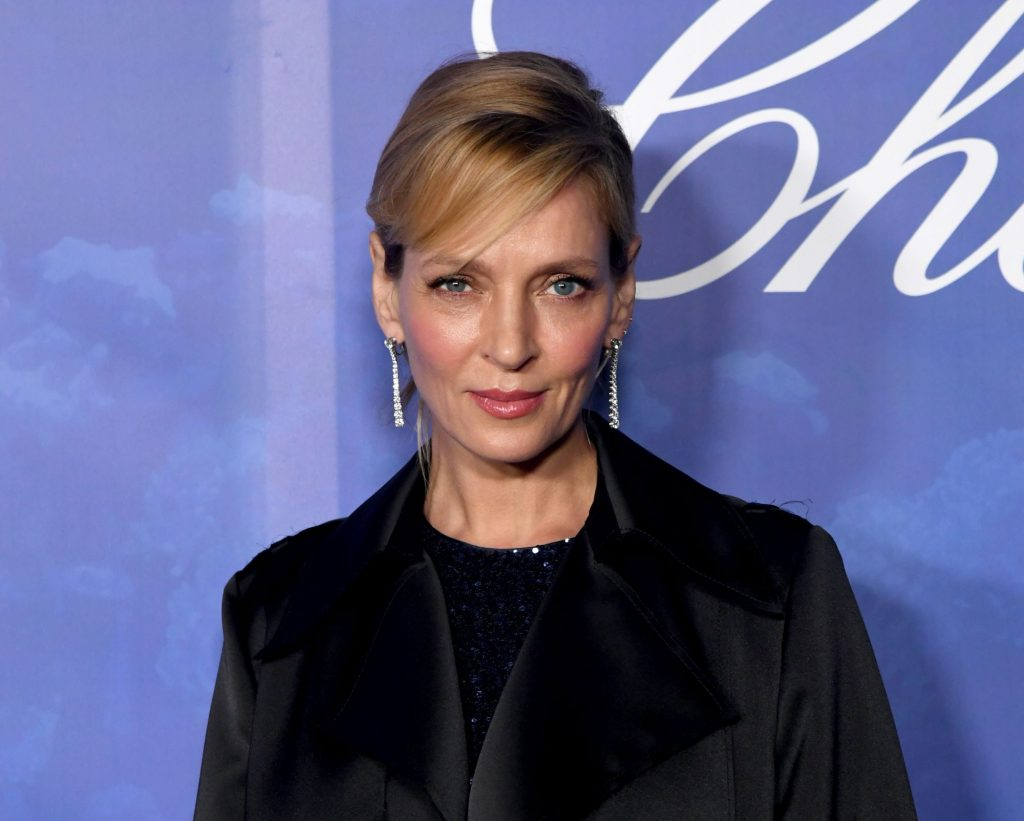 Uma Thurman wearing a black shirt with a black blazer in front of a blue background with cursive white writing.