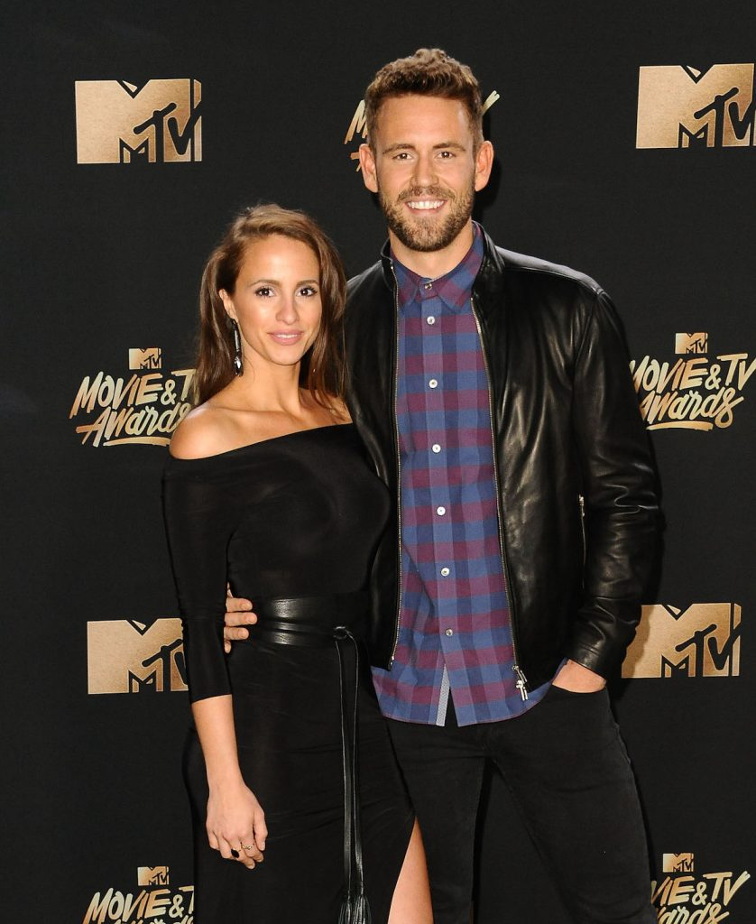 Vanessa Grimaldi and Nick Viall in matching formal black outfits pose for the camera at an event.
