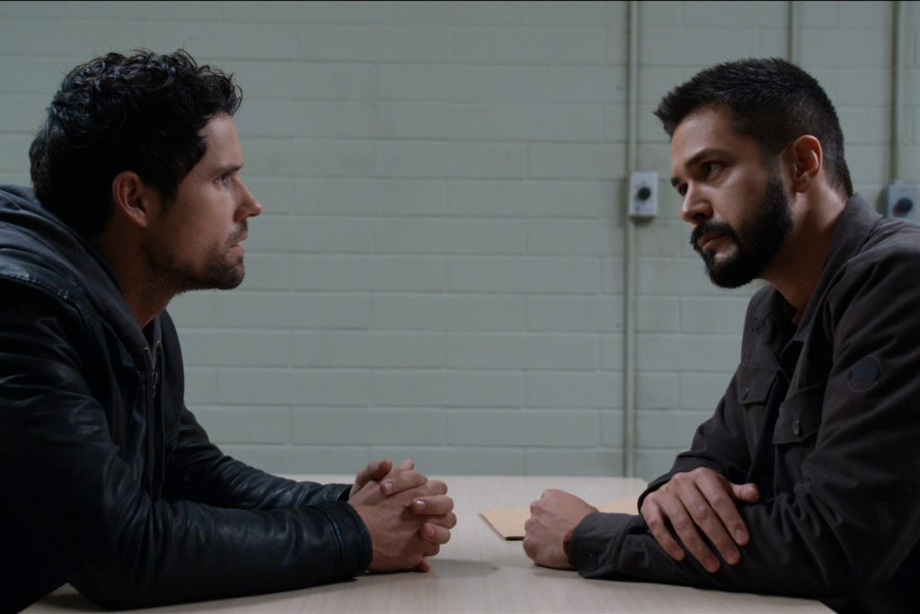 Ben Hollingsworth as Brady sits in the interrogation room with Marco Grazzini as Detective Mike Valenzuela in 'Virgin River'