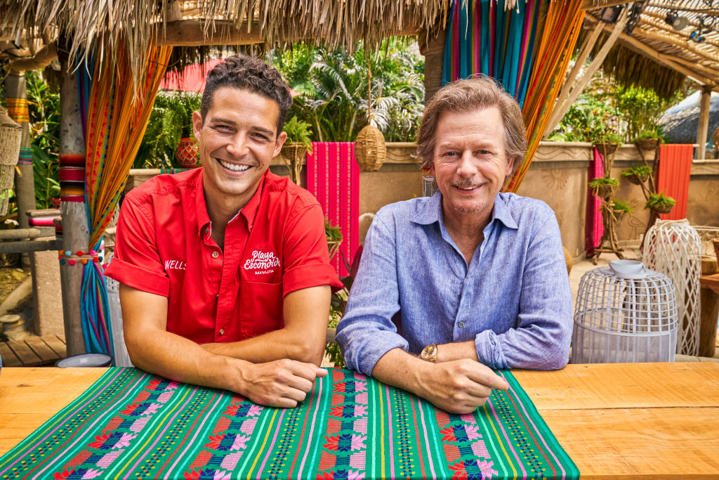 Wells Adams and David Spade pose for the camera, sitting side-by-side with smiles. Wells is dressed in a red shirt and David is wearing a light blue shirt.