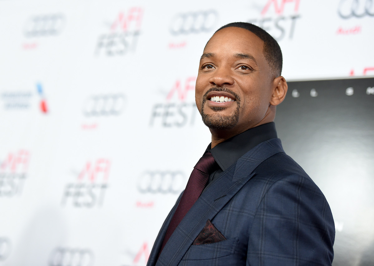Will Smith smiles and poses in a suit on the red carpet