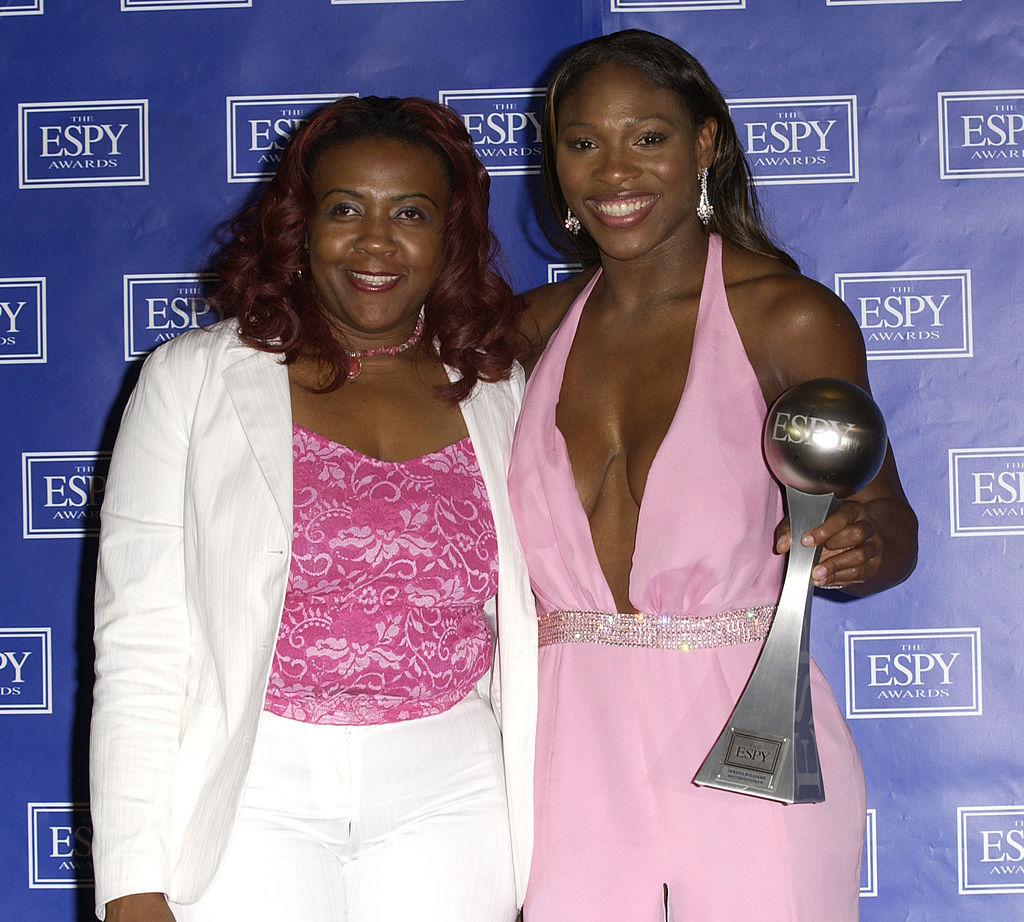 Tennis star Serena Williams and sister Yetunde Price pose for cameras at the ESPY Awards. Yetunde is wearing a white suit with a pink top, and Serena dazzles in a pink halter dress.