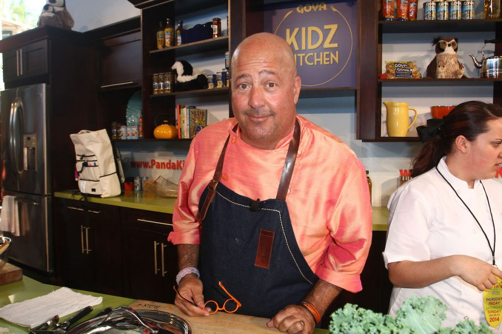 Andrew Zimmern stands in a kitchen