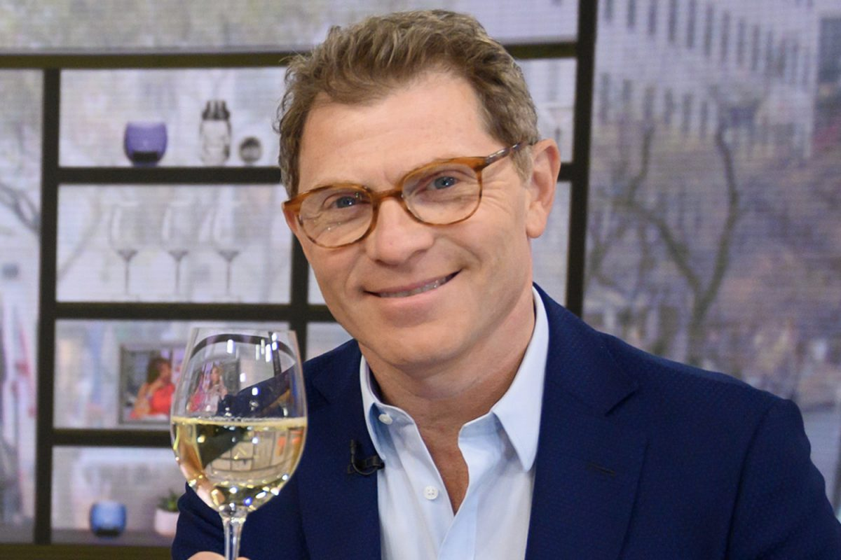 Bobby Flay wearing glasses and holding a wine glass