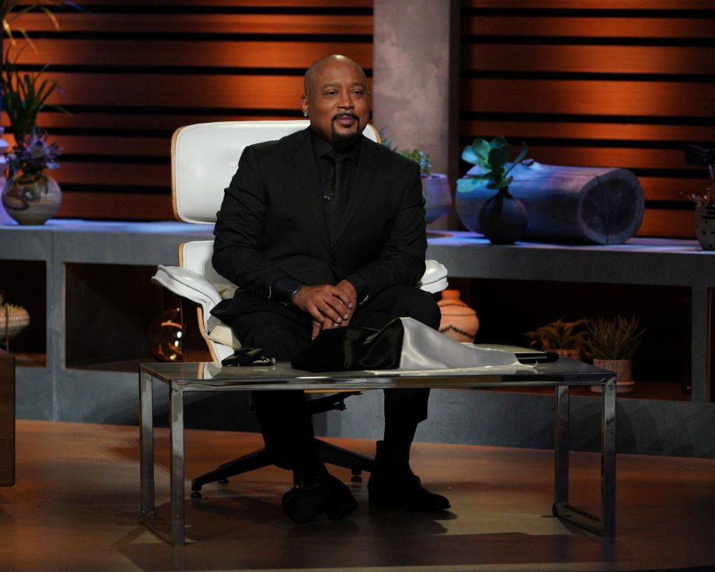 Daymond John sits in a chair on the set of Shark Tank