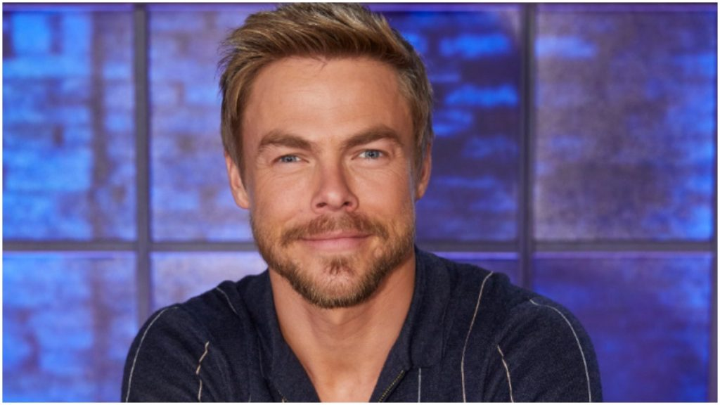 Derek Hough poses for a photograph in a black shirt.