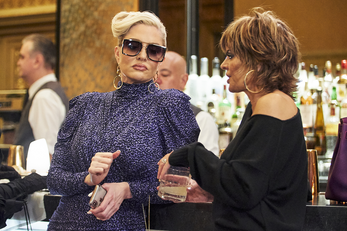 Erika Jayne leaning on a bar and wearing shades as Lisa Rinna speaks during a scene from 'RHOBH' Season 10