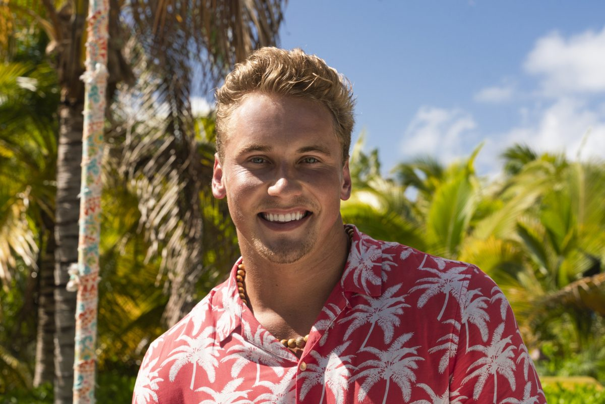 Garrett Morosky in a coral and white tropical shirt looking at the camera for an 'FBoy Island' bio photo.