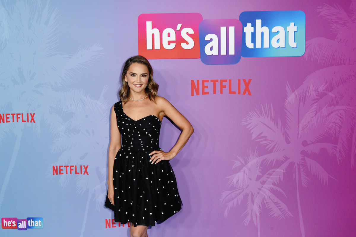'He's All That' actress Rachel Leigh Cook standing in front of a 'He's All That' step and repeat in a black, one shouldered dress.